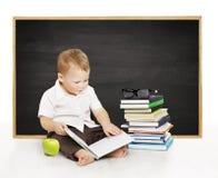 Libro di lettura dello scolaro vicino alla lavagna, ragazzo di scuola di asilo, Immagini Stock Libere da Diritti