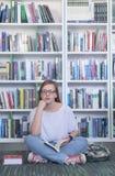 Libro di lettura dello studente di Famale in biblioteca Fotografia Stock