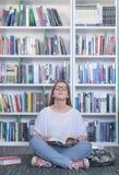 Libro di lettura dello studente di Famale in biblioteca Immagine Stock