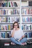 Libro di lettura dello studente di Famale in biblioteca Fotografie Stock Libere da Diritti