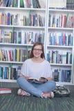 Libro di lettura dello studente di Famale in biblioteca Immagini Stock