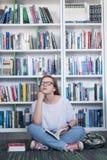 Libro di lettura dello studente di Famale in biblioteca Immagini Stock Libere da Diritti