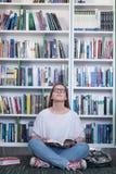 Libro di lettura dello studente di Famale in biblioteca Fotografia Stock Libera da Diritti