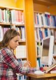 Libro di lettura di concentrazione grazioso dello studente facendo uso del computer Fotografia Stock Libera da Diritti