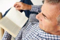 Libro di lettura di distensione del metà di uomo di età immagine stock