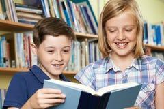 Libro di lettura di due allievi della scuola in biblioteca Fotografia Stock