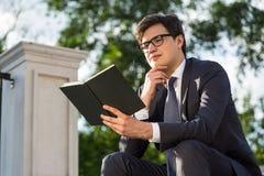 Libro di lettura di pensiero dell'uomo d'affari fuori Fotografia Stock