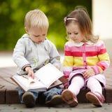 Libro di lettura divertente della ragazza e del ragazzo Fotografia Stock