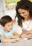 Libro di lettura elementare della scolara di età nella classe con l'insegnante Immagine Stock