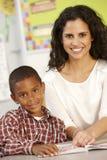 Libro di lettura elementare dello scolaro di età nella classe con l'insegnante Immagini Stock Libere da Diritti