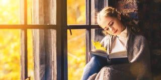 Libro di lettura felice della donna dalla finestra di autunno Fotografie Stock