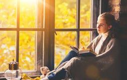 Libro di lettura felice della donna dalla finestra di autunno Immagine Stock