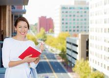 Libro di lettura felice della donna su un balcone del suo appartamento Fotografie Stock