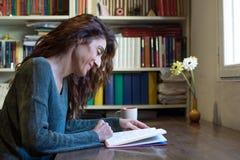 Libro di lettura felice della donna sulla tavola di legno Fotografia Stock