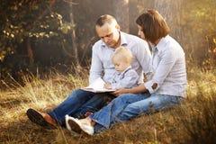 Libro di lettura felice della famiglia Immagine Stock Libera da Diritti