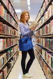Libro di lettura felice della ragazza dello studente in biblioteca Immagini Stock Libere da Diritti