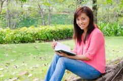 Libro di lettura felice tailandese della donna in sosta Immagine Stock