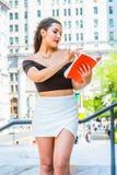 Libro di lettura femminile americano dello studente di college, studiante sulla città universitaria Immagine Stock