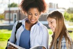 Libro di lettura femminile degli amici nella città universitaria dell'istituto universitario Fotografie Stock Libere da Diritti