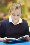 Libro di lettura femminile dell'allievo della scuola elementare in aula Immagine Stock Libera da Diritti