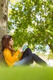 Libro di lettura femminile dell'istituto universitario contro il tronco di albero in parco Immagini Stock Libere da Diritti