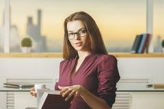 Libro di lettura femminile e caffè bevente Fotografie Stock