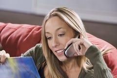 Libro di lettura femminile mentre parlando sul telefono Immagine Stock