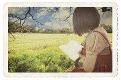 Libro di lettura femminile sotto l'albero Fotografia Stock Libera da Diritti