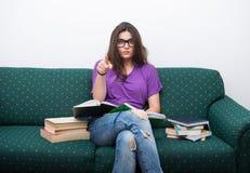 Libro di lettura femminile sveglio mentre sedendosi sullo strato Immagine Stock Libera da Diritti