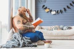 Libro di lettura grasso pensieroso dell'uomo Immagine Stock