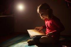Libro di lettura grazioso della bambina nel suo nascondiglio con il flashli fotografie stock