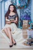 Libro di lettura grazioso della giovane donna nell'interno rustico Immagini Stock Libere da Diritti