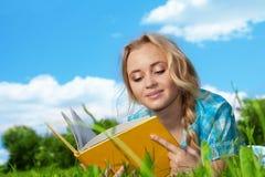 Libro di lettura grazioso della ragazza all'aperto Immagine Stock
