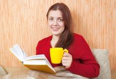 Libro di lettura grazioso della ragazza sul sofà Immagine Stock