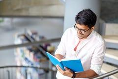 Libro di lettura indù del ragazzo o dell'uomo dello studente alla biblioteca Immagini Stock Libere da Diritti