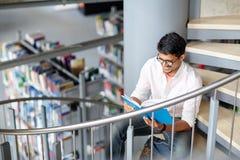 Libro di lettura indù del ragazzo o dell'uomo dello studente alla biblioteca Fotografie Stock Libere da Diritti