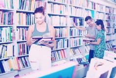 Libro di lettura interessato della ragazza dell'adolescente in deposito Fotografia Stock
