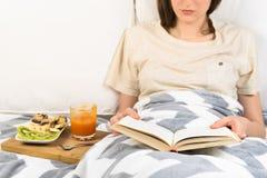 Libro di lettura a letto e mangiando prima colazione fotografia stock