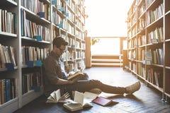 Libro di lettura maschio messo a fuoco in biblioteca Immagine Stock Libera da Diritti