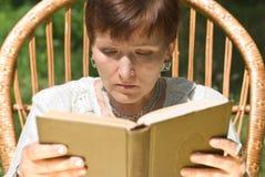Libro di lettura maturo della donna immagine stock