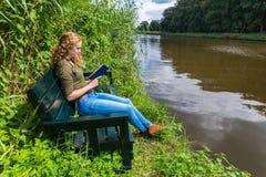 Libro di lettura olandese della donna sul banco ad acqua fotografie stock libere da diritti