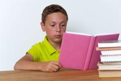Libro di lettura pensieroso del ragazzo della Tween a casa Fotografie Stock
