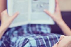 Libro di lettura pensieroso della ragazza Giovane donna sveglia che studia a casa, trovandosi sullo strato, spazio della copia immagini stock libere da diritti