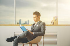 Libro di lettura premuroso dell'uomo d'affari Immagini Stock