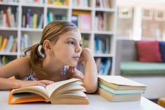 Libro di lettura premuroso della ragazza della scuola in biblioteca Fotografie Stock Libere da Diritti