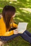 Libro di lettura rilassato della studentessa in parco Fotografia Stock
