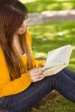 Libro di lettura rilassato della studentessa in parco Fotografie Stock