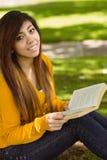 Libro di lettura rilassato della studentessa in parco Immagine Stock