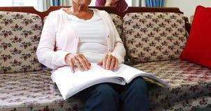 Libro di lettura senior della donna in Braille archivi video