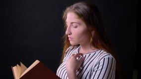Libro di lettura serio della giovane donna, tornitura capa e che osserva espressione premurosa e pensierosa della macchina fotogr stock footage